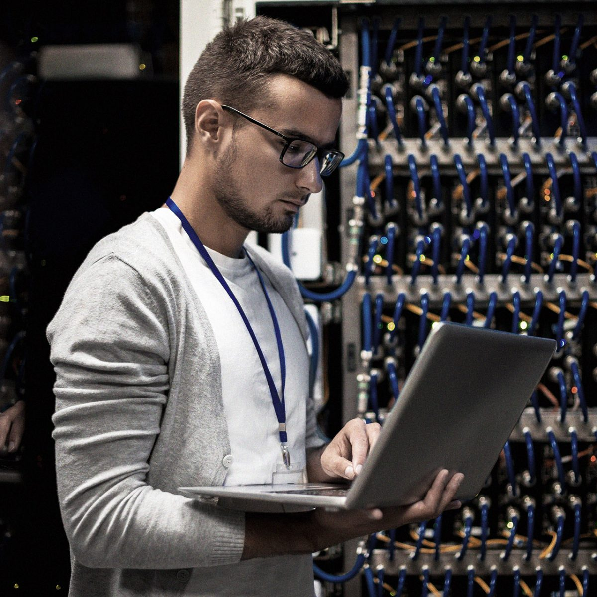 Side view portrait of young man with laptop standing by server cabinet while working with supercomputer