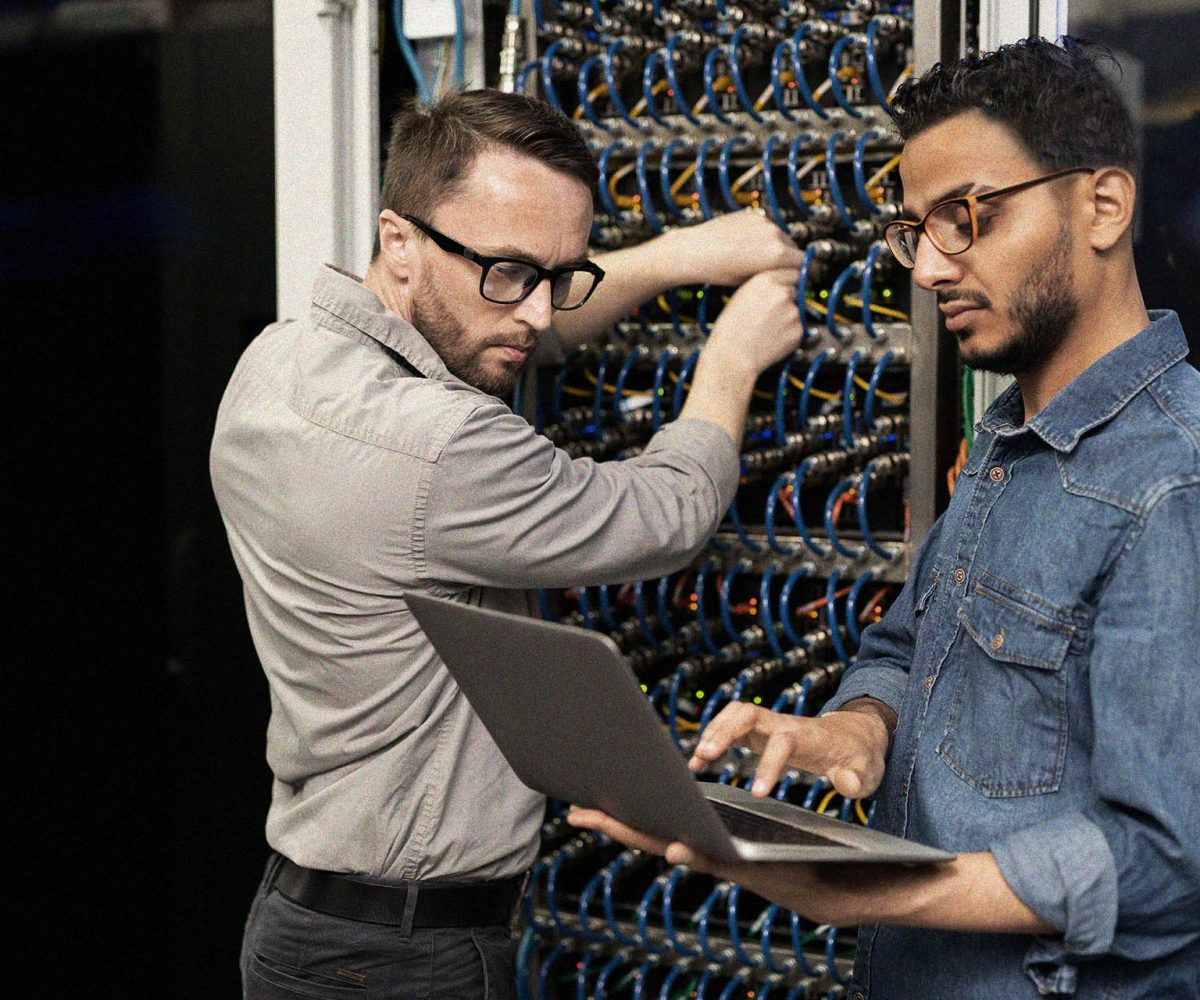 Serious young multi-ethnic IT engineers in casual shirts standing in database center and setting up computer cluster while examining information on laptop